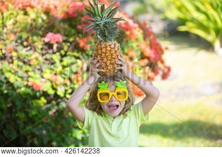 Funny Child Holds A Pineapple On Her Head On A Summer Nature Background. Pineapple Kid Boy And Pinea