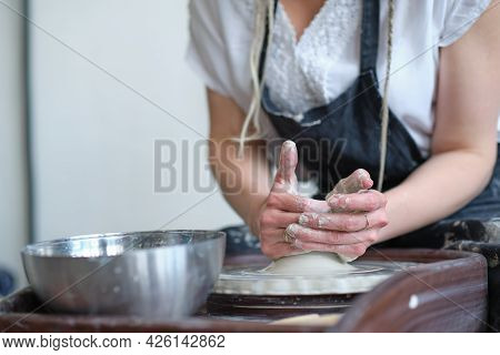 Close Up Female Hands Make Dishes From Clay. Woman Hands Working On Potters Wheel. The Master Potter