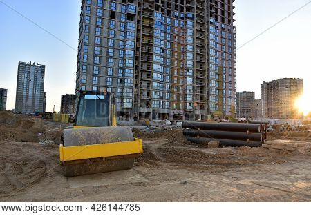 Soil Compactor Leveling Ground At Construction Site. Vibration Single-cylinder Road Roller On Constr