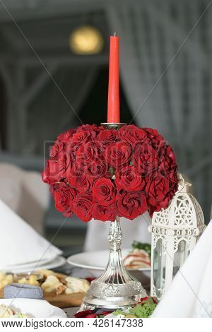 Silver Candlestick With A Red Candle And A Bouquet Of Red Roses