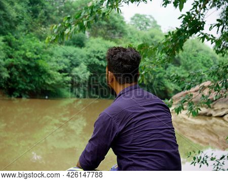 A Boy Seating Alone At River Bank, People Lifestyle Concept Image.