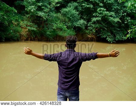 An Indian Boy Opening Hand Showing Happiness At River Bank On Natural Lifestyle Concept.
