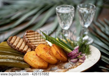 Classic Starter To Alcohol Shot. Platter With Snack And Two Glasses Of Vodka On Blurred Background.
