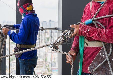 Industrial Worker Adjusting Climbing Gear Preparing Safety Rope.
