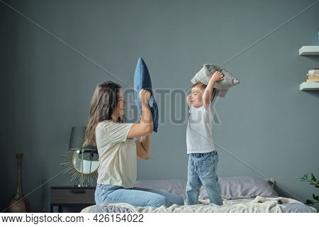 Funny Boy Throws Pillows At Mom, Pillow War, Happy Childhood. Motherhood, Maternity Leave Concept