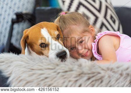 Child Cuddle A Dog On Backyard Sofa.