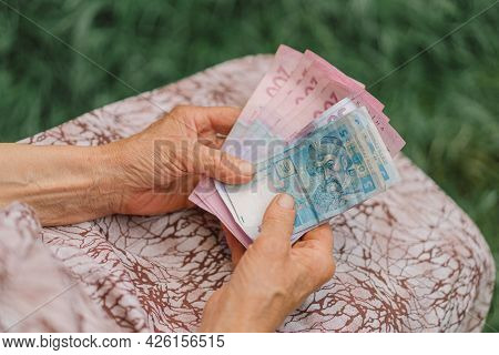 Concerned Elderly Woman Counting Ukrainian Money Hryvnia.