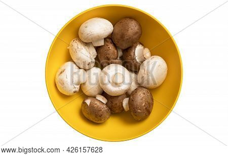 Fresh White And Brown Whole Mushrooms Champignon In Yellow Bowl Isolated On White Background