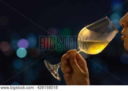 A Person Sniffing White Wine In A Glass For Wine Tasting With Colorful City Bokeh Lights Background.