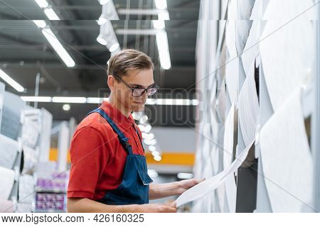 Salesman In A Wall Covering Store Checking The Markings On The Wallpaper .