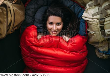 Portrait Of A Young Woman Who Is Cozy And Warm In A Red Sleeping Bag. Cute Tourist Girl With A Red S