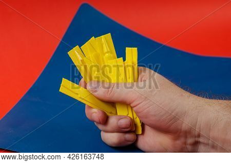 Male Hand Holds The Group Flea And Tick Drops Against Blue And Red. Yellow Plastic Container With Ve