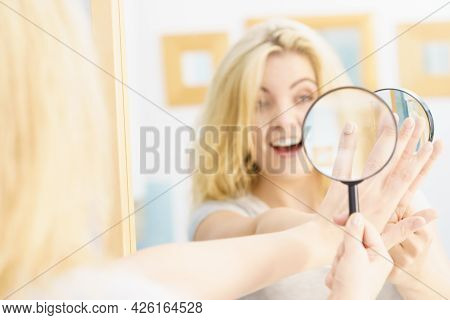 Beautiful Perfectionist Young Woman Checking Her Finger Nails Through Manifying Loupe Glass.