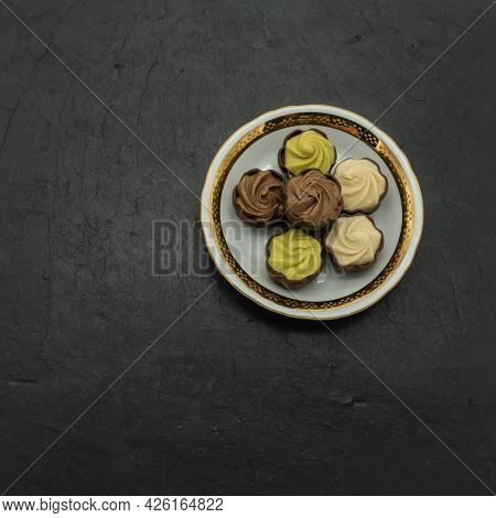 Chocolates With Creamy, Praline, Pistachio Filling Lie On A Porcelain Saucer With A Gold Border. The