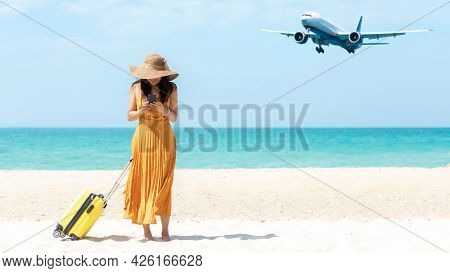 Asia Women Traveler Holding Yellow Luggage Walking And Check In Smart Phone On The Beach.  Traveling