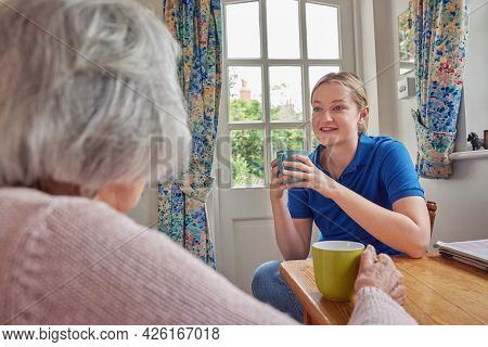 Female Home Help Having Cup Of Tea With Lonely Senior Woman In Kitchen