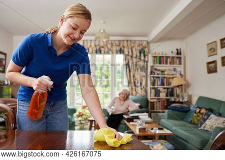 Female Home Help Cleaning House And Talking To Senior Woman