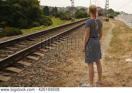 Crossing The Railway Tracks Across The Railway Tracks In The Daytime. Pedestrian Passing A Crosswalk
