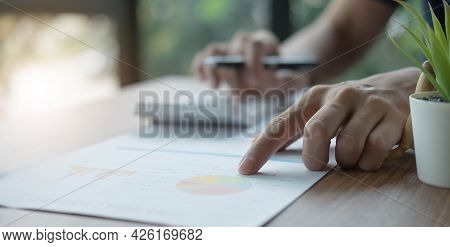 Businessman Pen Pointing Turnover With Graph Chart Report And Use Laptop Computer For Analysis Data