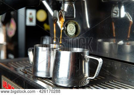 Makes Coffee. A Coffee Machine Pours Coffee Into A Pitcher.