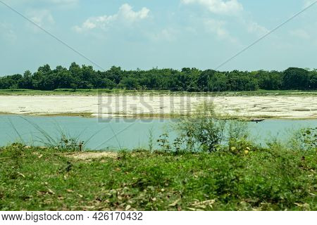 The River Channel And The Big Trees Surrounded By The Beautiful Greenery Of Rural Bengal Have Turned