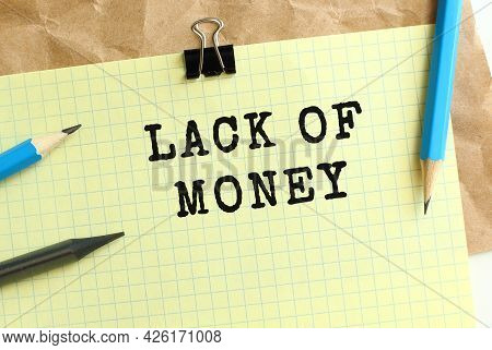 Lack Of Money Lettering On A Yellow Sheet Of Paper Over Crumpled Kraft Paper. Pencils And Paper Clip