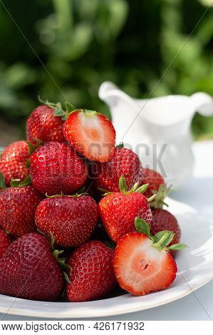 Blurred Image Of A Plate With Ripe Strawberries On A White Table With Daylight In The Nature Backgro