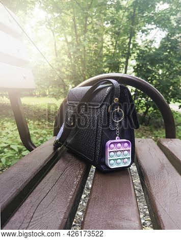 Antistress Toy Keychain Hanging On A Blue Bag, On A Park Bench. Silicone Stress Relief Toy