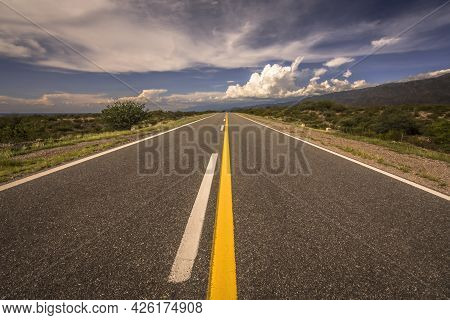 Empty Asphalt Road In The Middle Of Nowhere With Sunny Sky. Catamarca, Argentina  Empty Asphalt Road