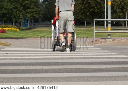 A Man Pushes Wheelchair With Disabled Through Pedestrian Crossing