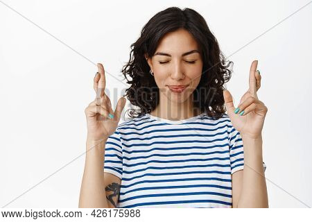 Image Of Happy Optimistic Girl Making Wish, Close Eyes And Cross Fingers While Anticipating, Praying
