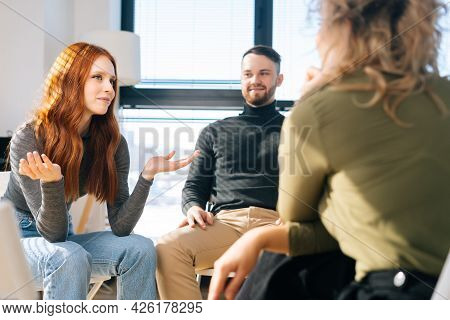 Young Successful Coworkers Sitting On Chairs In Circle, Discussing Working Or Personal Issues Togeth