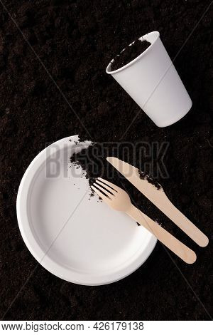Paper Plate And Glass, Wooden Fork And Knife On Soil Close-up, Top View. Compostable Or Biodegradabl