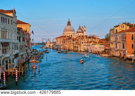 Panorama of Venice Grand Canal with gondola boats and Santa Maria della Salute church on sunset from Ponte dell'Accademia bridge. Venice, Italy