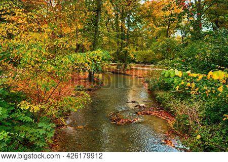 Munich English garden Englischer garten park. Autumn colours on trees and leaves and flowing river. Munchen, Bavaria, Germany