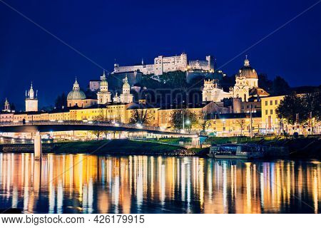 Salzburg city evening view. Cathedral, Old Town Altstadt, Hohensalzburg castle illuminated at night. Salzach River waterfront with promenade. Salzburg, Austria