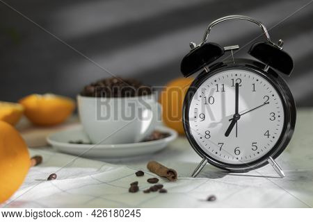 The Retro Alarm Clock Indicates 7:00 Am And Is Illuminated By Rays Of Morning Light Through The Blin