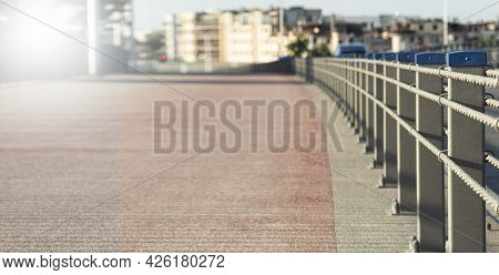 The Running Track Is Fenced Off From The Carriageway. Fencing By Columns And A Cable Of The Sidewalk