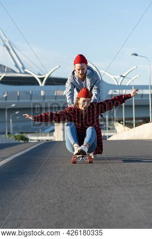 Young Adult Couple Have Fun On Longboard Outdoors Riding City Road. Cheerful Laughing Female Sit On