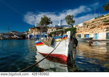 Fishing boats moored in crystal clear turquoise sea water in harbour in Greek fishing village of Mandrakia, Milos island, Greece. Horizontal camera pan