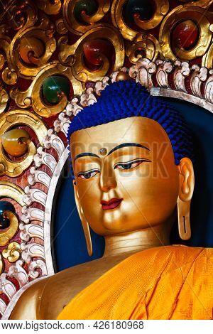 Gilded statue of Sakyamuni Buddha in Buddhist Tsuglagkhang temple gompa. McLeod Ganj, Himachal Pradesh, India