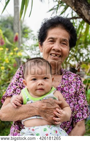 Adorable Baby Boy Looking At Camera With Interest On Arm Of Grandmother. Little Asian Newborn Lookin