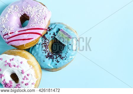 Fresh Donuts With Colored Glaze On A Blue Background Of Kopi Space. Colorful Donuts Close-up