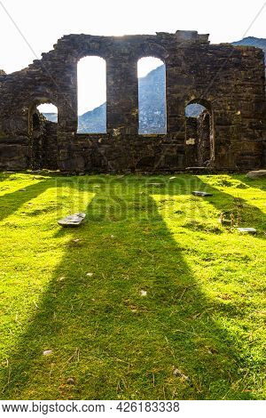 Spectacular Sun Behind Ruined Gothic Church, Throwing Bright Light Onto Green Grass.