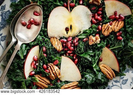 Kale salad with pomegranate and apple with pecans food photography