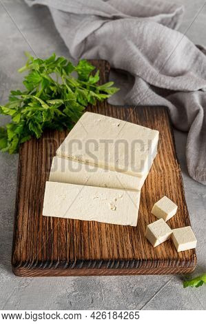 Fresh Cheese Tofu From Soybeans With Parsley On A Board On A Gray Concrete Background. A Vegan Produ