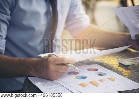 Hand Of Financial Advisor Point And Review Budget Report. Professional Businessman Write And Analysi