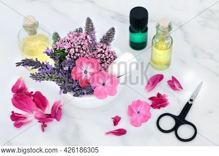 Naturopathic herbal medicine with summer flowers and herbs in a mortar and pestle with oil bottles and rose petals on marble. Natural health care concept for aromatherapy essential oil preparation.