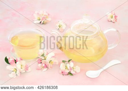 Apple blossom flower herbal tea high in antioxidants, beneficial for digestion, obesity, nervous system and skin ailments problems. Health care concept On pink marble.