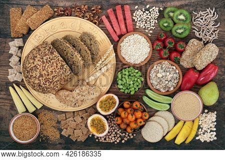 Vegan health food very high in dietary fibre with fruit, vegetables, nuts, seeds, legumes, cereals  grain products. Immune boosting healthy foods on rustic wood background. Flat lay. Top view.